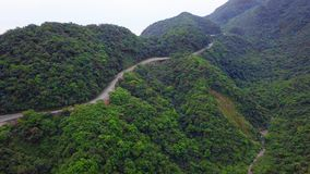 Car Moving along Curved Serpentinous Road among Green Lush Forest Trees in Taiwan. Aerial View. Shot with a DJI Mavic fps 29,97 4k stock footage