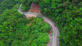 Car Moving along Curved Serpentinous Road among Green Lush Forest Trees in Taiwan. Aerial View. Shot with a DJI Mavic fps 29,97 4k stock video