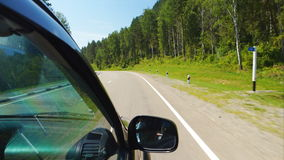 Car is moving along the forest and mountain (POV). POV: Car is moving along the forest and mountain on a highway in Altay, Russia stock video