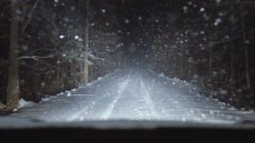 The car is moving along a forest snow-covered road. Snowflakes fall on the windshield of the car. It`s snowing in the forest stock footage