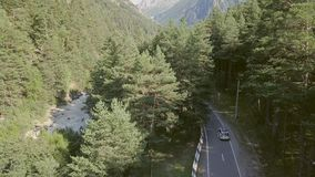 Car moving along highway among forest and mountains. Car trip family on vacation. Car moving along highway among forests and mountains. Top view car driving on stock footage