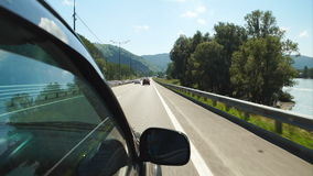 Car is moving along the Katun river in Altay (POV). POV: Car is moving along the Katun river on a highway in Altay, Russia stock video