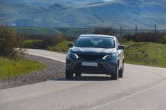 Car is moving along a winding road. In a mountainous area royalty free stock photo
