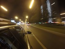 The car is moving at high speed on the night road in the city. Stock Photography
