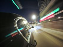 The car is moving at high speed on the night city road. Royalty Free Stock Image