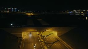 Car moving on highway tunnel with night lighting on background modern city. Architecture. Car traffic on night highway road in city infrastructure drone view stock video