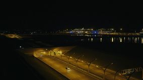 Car moving in highway tunnel past ships in sea port in modern city drone view. Car traffic on urban highway and road sign with street names on background night stock video