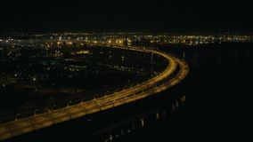 Car moving on modern highway bridge with night lighting in city of the future. Car moving on modern highway bridge with night lighting past sea port in city of stock video