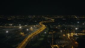 Car moving on night bridge past ships in sea port in modern city of the future. Car traffic on night highway in city infrastructure aerial view stock video footage