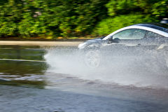 Car moving through puddle Stock Photography
