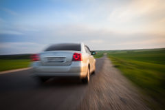 The car is moving rapidly toward the horizon. The car is moving rapidly towards the horizon past the green fields royalty free stock photo