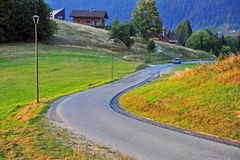 Car moving by the rural road. DONOVALY, SLOVAKIA - SEPTEMBER 20: Car moving by the rural road in Donovaly village, Slovakia on September 20, 2018 stock image