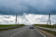 Car moving up the hill on country road on overcast summer day in Royalty Free Stock Photos