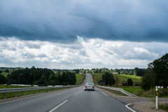 Car moving up the hill on country road on overcast summer day Royalty Free Stock Photos