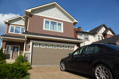 Car near garage of new two-storied cottage Royalty Free Stock Images