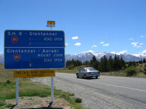 Car on New Zealand highway. Scenic view of car travelling on New Zealand highway to Mount Cook, signpost in foreground and mountains in background Royalty Free Stock Photo