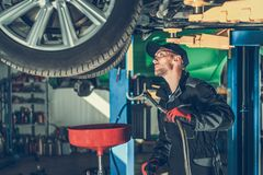 Car Oil Change in the Service. Car Oil Change in the Auto Service. Caucasian Mechanic Preparing Equipment To Remove Old Oil From the Vehicle Engine stock photography