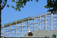 Car on old wooden roller coaster. Car of riders on rails of old wooden roller coaster against blue skies on sunny day stock images