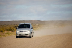 Car on an open dusty road. Car driving down a gravel road, dust can be seen in the vehicles wake Stock Photo