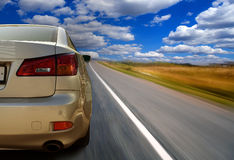 Car on open highway. A partial view of the rear a white car, speeding down an open highway Royalty Free Stock Images