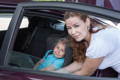 Car opened door with helping mother to fast small child Stock Images