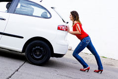 Car out of gas. Woman pushing car out of gasoline Stock Images