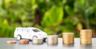 Car over a lot of stacked coins. declining profits in the automo Royalty Free Stock Image