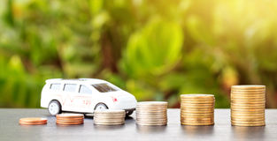 Car over a lot of stacked coins. Royalty Free Stock Images