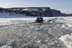 The car overcomes a water barrier of ice. Indigirka River. Yakutia. Russia stock image
