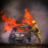 Burning car and firefighter. British fire fighter sprays water on burning car during an exercise Royalty Free Stock Image