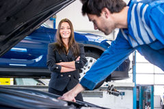 Car owner happy with instant service by a professional mechanic. Young, pretty businesswoman looks happily at the mechanic, whilst he's fixing her car in stock photography
