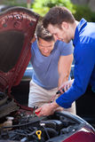 Car Owner With Mechanic Testing Car Battery Royalty Free Stock Photography
