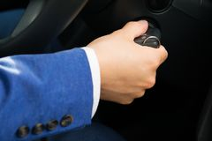 The car owner`s hand turns the cars ignition key, in a blue suit. The car owner`s hand turns the car`s ignition key, in a blue suit Stock Images