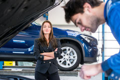 Car owner waiting on a mechanic to finish fixing her car Royalty Free Stock Photo