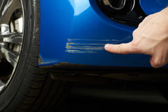 Car paint scratch. Close-up. Finger show scratch on blue car royalty free stock photos