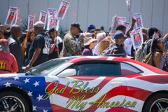Car painted with american flag colors in front of protestors Stock Image