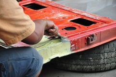 Car painter. Auto mechanic preparing the front bumper of a car for painting Stock Photos
