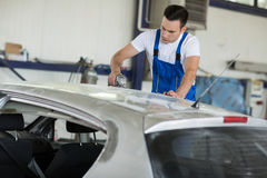 Car painter fixing damage. On car Royalty Free Stock Image