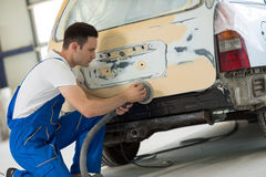 Car painter polishes body part Stock Photography
