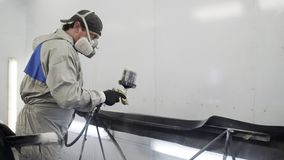 Car painter spraying black paint on car body part. Auto painter with spray gun covering car body part with black paint stock footage