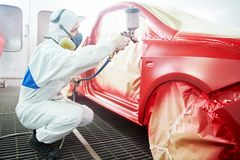Car painting technology. Auto mechanic worker painting a red car in a paint chamber during repair work