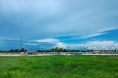 Car park beside green rice field under cloudy blue sky Stock Image