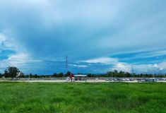 Car park beside green rice field under cloudy blue sky Royalty Free Stock Image