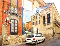 Car parked along a colored facade with street art mural. Stock Photo