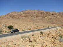 Car parked on desert road Stock Image