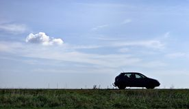 Car parked in a field. A picture of a car, parked in an open field under the clear blue sky. A small cloud drifts in its direction Stock Photo