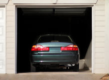 Car parked in a garage. Rear view of a car parked inside of a residential garage Stock Image