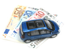 Car parked on money. A miniature car parked on some money Stock Images