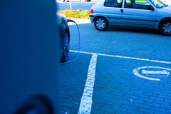 Car parked on the parking. Charging an electric car with electricity. A hidden camera in the parking lot behind the car. royalty free stock photos