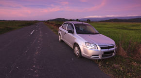 Car parked on roadside at sunset in a rural area Royalty Free Stock Photo